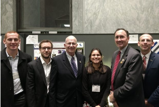 Standing in front of a research display are Andrew Treleaven, Alessandro Alabastri, U.S. Rep. Ted Poe, Pratiksha Dongare, U.S. Rep. Pete Olson and Nathan Cook.