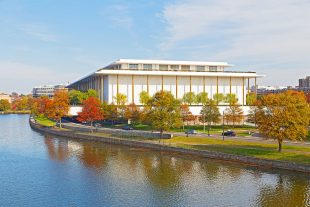 34082224 - kennedy performing arts center in autumn, washington dc. modern building of kennedy center and colorful trees are reflected in potomac river.