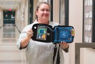REMS Director Lisa Basgall recently installed an AED in George R. Brown Hall.
