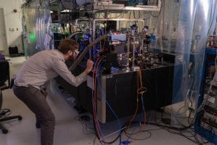 Physicist Tom Langin makes an adjustment to an laser-cooling experiment