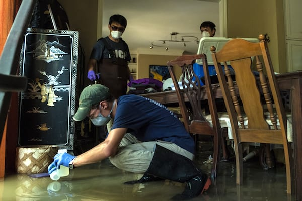Rice University students collect water samples from a flooded Houston home after Hurricane Harvey in 2017. Rice researchers have issued the first report to quantify levels of contamination in floodwaters and sediments deposited by the storm. (Credit: Jeff Fitlow/Rice University)