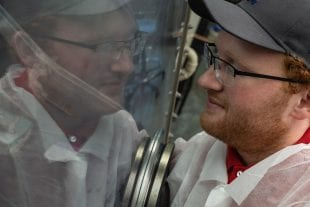 Applied physics graduate student Kyle Chapkin working at a glove box