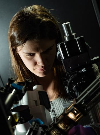 Rice University graduate student Lauren McCarthy adjusts the polarizer she used to discover a fundamentally different form of light-matter interaction in their experiments with gold nanoparticles. (Credit: Jeff Fitlow/Rice University)