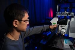 Rice University graduate student Yi-Yu Cai adjusts a microscope to focus on gold nanorods, the target of new research into the source of useful light emissions from metal nanoparticles. (Credit: Photo by Jeff Fitlow)