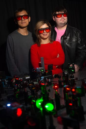 Rice University researchers are looking into the source of light emitted by plasmonic metal nanoparticles. In a new paper, they argue for the dominance of photoluminescence as opposed to Raman scattering. From left: Yi-Yu Cai, Behnaz Ostovar and Lawrence Tauzin. (Credit: Jeff Fitlow/Rice University)