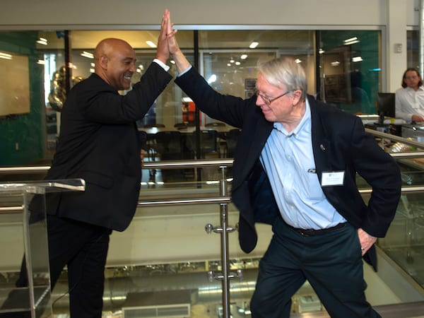Reginald DesRoches, the William and Stephanie Sick Dean of Engineering, left, get a high-five from his predecessor, Ned Thomas, at the OEDK party. Photo by Jeff Fitlow
