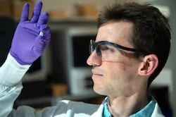 Rice University graduate student Sean Bittner holds a sample of a 3D-printed scaffold that may someday help heal osteochondral injuries of the kind often suffered by athletes. The material mimics the gradient structure of cartilage to bone found at the end of long bones. (Credit: Jeff Fitlow/Rice University)