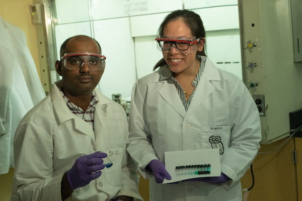 Rice University research scientist Babu Ganguli and graduate student Kimmai Tran show test tubes with their eutectic solvent and varying concentrations of cobalt drawn into the solution. They are developing the solvent to extract cobalt and lithium from spent lithium-ion batteries. (Photo by Jeff Fitlow/Rice University)
