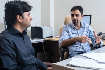 Rice University graduate student Prabhas Hundi, left, and Rouzbeh Shahsavari, an assistant professor of civil and environmental engineering, are using deep learning techniques to speed up simulations of novel two-dimensional materials to understand their characteristics and how they're affected by high temperature and radiation. (Credit: Jeff Fitlow/Rice University)