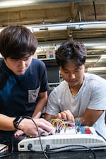 Takanori Iida, left, and Byung-UK Kang, senior engineering students at Rice University, work on the electronics test bed used to design a device that helps doctors secure rods that keep fractured bones in alignment. A sensor attached to a movable track finds the right spot to drill by pinpointing holes in the rod marked with magnets. (Credit: Jeff Fitlow/Rice University)