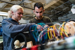 Hannah Jackson and Will Yarinsky, senior engineering students at Rice University, make an adjustment to their device to help doctors secure rods that keep fractured bones in alignment as they heal. (Credit: Jeff Fitlow/Rice University)