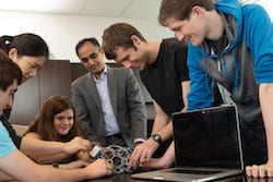 Members of the Axon Mobile team of Rice University engineering students gather with their adviser, Dr. Nitin Tandon, to discuss progress on their wireless monitor to record seizure data from patients with intractable epilepsy. From left: Andres Gomez, Irene Zhang, Sophia D'Amico, Tandon, Benjamin Klimko, and Aidan Curtis. (Credit: Jeff Fitlow/Rice University)
