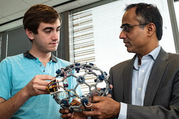 Rice University engineering student Andres Gomez and Dr. Nitin Tandon of the McGovern Medical School at The University of Texas Health Science Center at Houston hold a cap with sensors used to develop a wireless monitor that records seizure data from patients with intractable epilepsy. (Credit: Jeff Fitlow/Rice University)