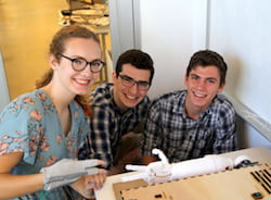Rice University students -- from left, Liz Kacpura, Noah Kenner and Caz Smith – demonstrate their Ro Sham Bot, a rock-paper-scissors robot, at an exhibition by engineering students of mechatronic art at Rice's Moody Center for the Arts. (Credit: Donald Soward/Rice University)
