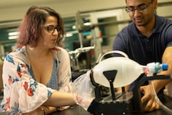 Engineering students Natalie Dickman and Aravind Sundaramraj adjust their automated bag valve mask device at Rice University's Oshman Engineering Design Kitchen. (Credit: Jeff Fitlow/Rice University)