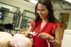 Rice University engineering student Carolina De Santiago sets up a mannequin to receive air from the automated bag valve mask device she and her teammates designed and built. The team hopes its work will help save lives where and when ventilators are not available. (Credit: Jeff Fitlow/Rice University)