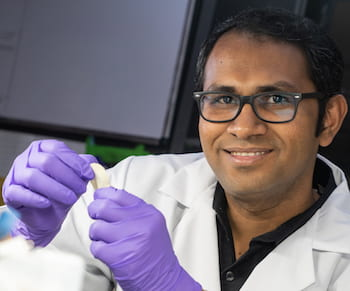 Rice University research scientist M.M. Rahman holds a flexible dielectric made of a polymer nanofiber layer and boron nitride. The new material stands up to high temperatures and could be ideal for flexible electronics, energy storage and electric devices where heat is a factor. (Credit: Jeff Fitlow/Rice University)