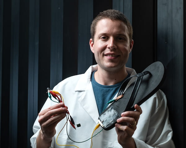 Rice University postdoctoral researcher Michael Stanford holds a flip-flop with a triboelectric nanogenerator, based on laser-induced graphene, attached to the heel. Walking with the flip-flop generates electricity with repeated contact between the generator and the wearer's skin. Stanford wired the device to store energy on a capacitor. (Credit: Jeff Fitlow/Rice University)