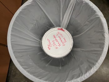 A plastic bucket and a plastic bag contain a 5-gallon supply of carbon nanotubes in a lab at Rice University, representing the beginning of the process to safely transfer the nanotubes for experimental use. The Rice lab published its technique in SN Applied Sciences. (Credit: Barron Research Group/Rice University)
