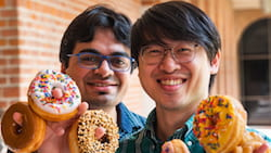 "Rice University graduate students Nitant Gupta, left, and Henry Yu performed theoretical calculations that showed how the ""donuts"" on a growth substrate influence the electronic behavior of two-dimensional materials. The resulting localized strain could help researchers tune the properties of the material for applications like quantum information systems. (Credit: Jeff Fitlow/Rice University)"