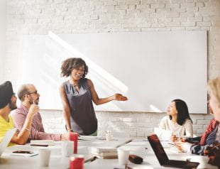 Woman presenting to boss and coworkers at meeting. Photo credit: 123rf.com.