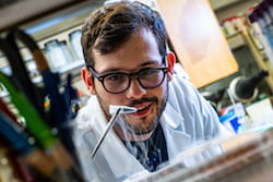 Rice University graduate student Ian Campbell pulls a vial of ferredoxin proteins from cold storage. The iron and sulfur proteins, believed to be present at the start of life on Earth, facilitate the transfer of energy in cells. The Rice experiments showed synthetic biologists may use them to control electron transfer in cells. (Credit: Jeff Fitlow/Rice University)