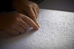 A child reads braille. Photo credit: 123rf.com