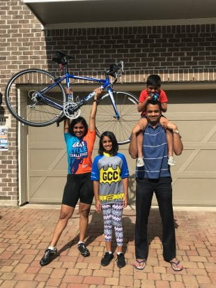 Sudha Yellapantula, left, raises her bike in triumph alongside her family after finishing 600 miles in a month.