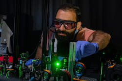 Rice University graduate student Seyyed Ali Hosseini Jebeli works in the laser lab where he and his colleagues confirmed that plasmons can be used to heat one or the other of a pair of electromagnetically linked gold nanoparticles. The ability to control heat at the nanoscale has potential applications in heat-assisted magnetic recording, photothermal therapies and temperature-driven reactivity. (Credit: Jeff Fitlow/Rice University)