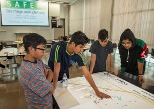 Gulton-area middle school students look at a map of pedestrian safety. Photo by Tommy LaVergne.