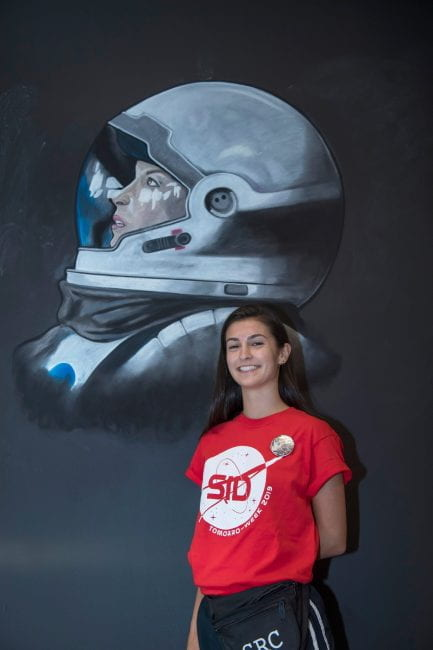 "Fernanda ""Fern"" Horrillo poses in front of her chalk drawing for Sid Richardson College's O-Week theme. (Photo by Tommy LaVergne)"