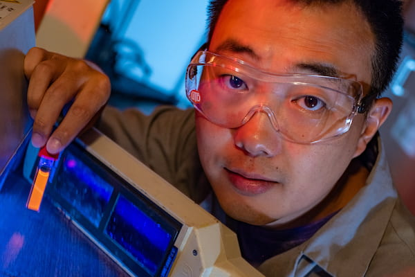Rice University graduate student Bo Jiang shows a fluorescing vial of soluble amyloid beta peptide aggregates implicated in the onset of Alzheimer's disease. The peptides are tagged and tracked with a ruthenium complex developed at Rice that can monitor them in lab experiments as they grow over time. (Credit: Jeff Fitlow/Rice University)