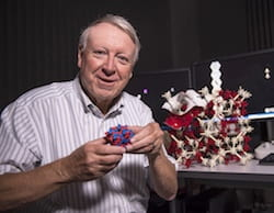 Rice University materials scientist Ned Thomas holds a model of the block copolymer he and his lab created to see if the cubic structures within were perfect or not. Examination with an electron microscope showed distortions in the lattice that could affect their photonic and phononic properties. (Credit: Tommy LaVergne/Rice University)