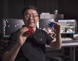 "Rice University postdoctoral researcher Xueyan Feng holds ""left"" and ""right"" chiral models of the block copolymer double gyroid created in the lab of materials scientist Ned Thomas. The double gyroid lattice turned out to be less than perfect, as demonstrated by slicing away nanoscale layers of the polymer and imaging it with an electron microscope. (Credit: Tommy LaVergne/Rice University)"