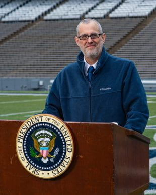 "David Ruth stands with the podium used by President John F. Kennedy during his ""We choose to go to the moon"" speech in Rice Stadium. Photo by Jeff Fitlow."