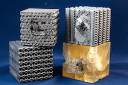 Tubulane-like polymer structures created at Rice University were better able to handle the impact of a bullet than the polymer reference cube at bottom right. The bullet stopped in approximately the second layer of the tubulane structures, with no significant structural damage observed beyond that layer. Bullets fired at the same speed sent cracks through the entire reference cube. (Credit: Jeff Fitlow/Rice University)