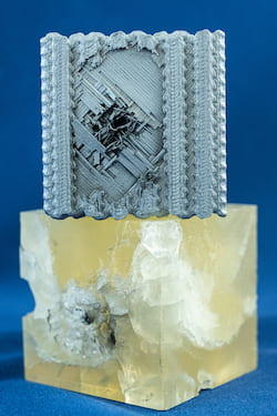 Materials made at Rice University based on theoretical tubulane structures were better able to handle the impact of a bullet than the polymer reference cube at bottom. The bullet stopped in approximately the second layer of the tubulane structures, with no significant structural damage observed beyond that layer. Bullets fired at the same speed sent cracks through the entire reference cube. (Credit: Jeff Fitlow/Rice University)
