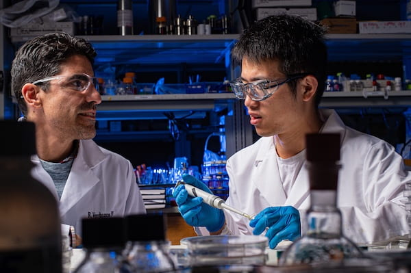 Rafael Verduzco, left, a chemical and biomolecular engineer at Rice University, and graduate student Hao Mei led a study that shows microscopic bottlebrush polymers are drawn to the top and bottom of a coating applied to a surface. The discovery could lead to a way to customize the properties of coatings for specific applications. (Credit: Jeff Fitlow/Rice University)