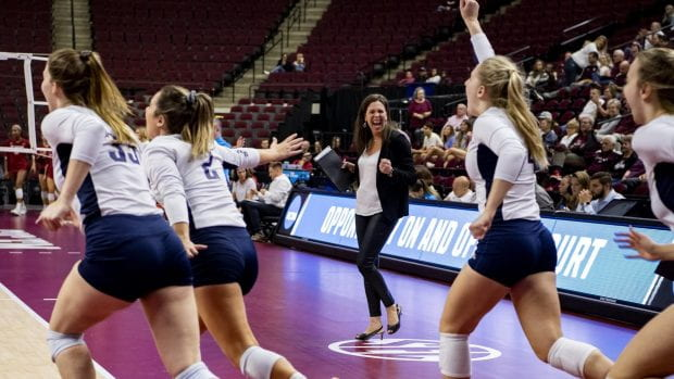 Head coach Genny Volpe (middle) and the Rice volleyball team celebrates its victory over Oklahoma Dec. 5 in College Station, Texas. (Photo by Maria Lysaker/Rice Athletics)