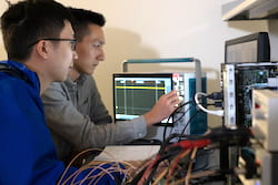 Rice University graduate students Joshua Chen, left, and Zhanghao Yu test a prototype neural implant that can be programmed and charged remotely with a magnetic field. The chip may make possible imbedded devices like a spinal cord-stimulating unit with a battery-powered magnetic transmitter on a wearable belt. (Credit: Jeff Fitlow/Rice University)