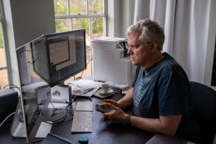 Karl Ecklund, professor of physics and astronomy, prepares his home office for delivering remote instruction. (Photo by Brandon Martin)