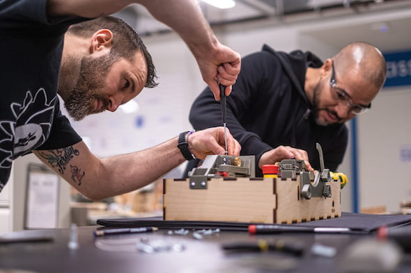 Danny Blacker, left, and Fernando Cruz, staffers at Rice University's Oshman Engineering Design Kitchen, assemble a prototype of the ApolloBVM bag valve mask automation device. (Credit: Jeff Fitlow/Rice University)
