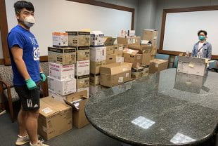 Graduate students Yuren Feng and Xiaochuan Huang with boxes of masks, gloves and other protective gear and lab testing supplies that Rice laboratories donated to the University of Texas Health Science Center at Houston April 1.