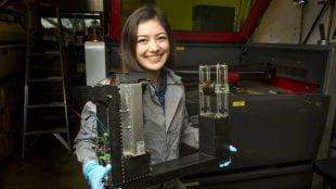 Cofer holds the 3D graphene printer she built in James Tour's lab.