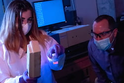 Rice University graduate student Ashleigh Smith McWilliams and chemist Angel Martí view fluorescing boron nitride nanotubes. Their analysis of the nanotubes' motion will help scientists better understand particle behavior in the likes of liquid crystals, gels and polymer networks. (Credit: Jeff Fitlow/Rice University)