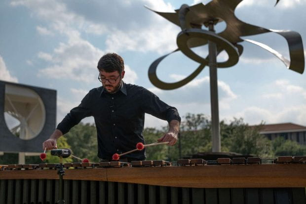 Shepherd School percussionist Aaron Smith performs a new composition by Shepherd School composer Theo Chandler inspired by Mark di Suvero's Po-um (Lyric) (2003). Photo by Daniel Ortiz
