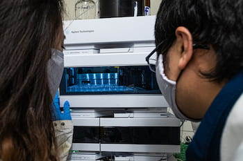 Rice University graduate student Shuyuan Yang, left, and postdoctoral researcher Fanglong Zhao check samples as they work to isolate molecular drug scaffolds from fungus. (Credit: Jeff Fitlow/Rice University)
