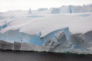 Blocks of dense, blue ice the size of convenience stores can be seen breaking away from Thwaites Glacier in a February 2019