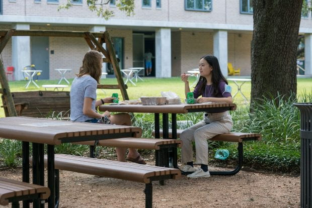 Li enjoys lunch with her roommate in the Will Rice College courtyard.