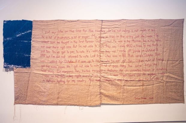 "Clinton Drake's words are embroidered with red thread on McMillian's ""Untitled (flag IV)."""
